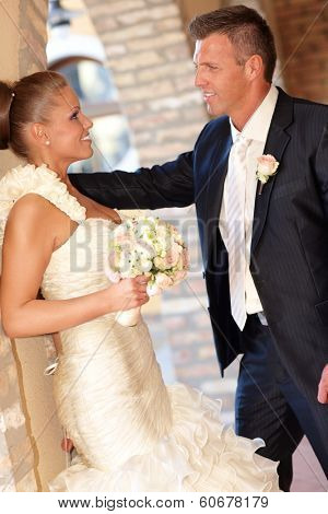 Side view of young couple on wedding-day, smiling happy outdoors, bride leaning against wall.