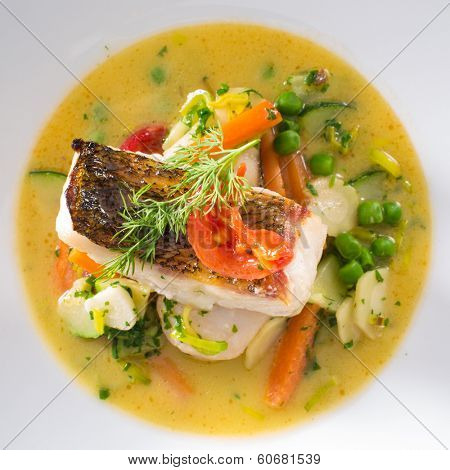 Baked pike perch fish with saute vegetables and sauce. Delicious gourmet food. Isolated.