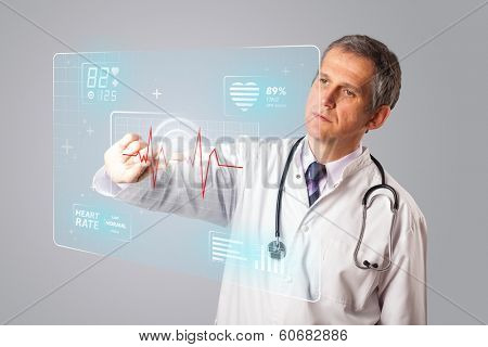 Middle aged doctor standing and pressing modern medical type of button