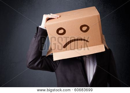 Businessman standing and gesturing with a cardboard box on his head with sad face