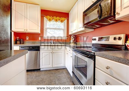 Cozy Kitchen Room With Red Wall And White Cabinets