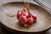 pic of red shallot  - Still Life With Shallots red onions in wood bowl.