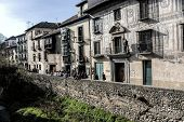 People Leaned Out And The Balconies Of A Nineteenth Century Facade At The Feet Of The River Darro