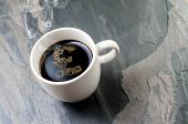 Coffee cup-Pound Sterling sign on stone table