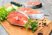 picture of plate fish food  - Raw salmon fish steaks with fresh herbs on cutting board