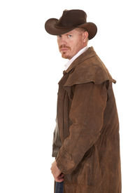 stock photo of wrangler  - A cowboy in a leather coat looking back over his shoulder - JPG