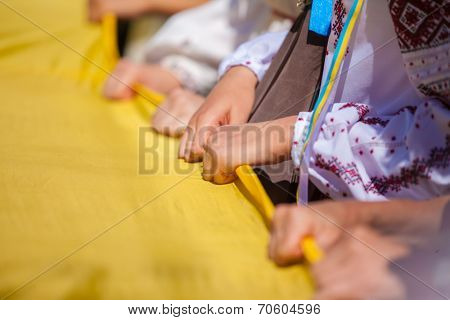 ODESSA, UKRAINE - August 23: Flash mob in city of Odessa on Potemkin Stairs on August 23, 2014, in day of a national flag of Ukraine. Hands of participants of Flash mob in Odessa with a flag