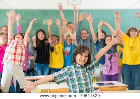 Group of kids having up rising hands with books in classroom