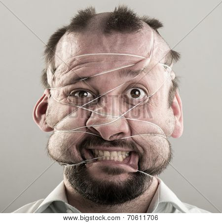 Ugly man tied with strings on his face