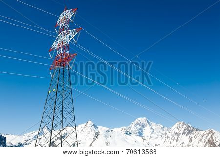 High voltage power lines in winter mountain landscape - Mont Blanc, the Alps, France, Europe.