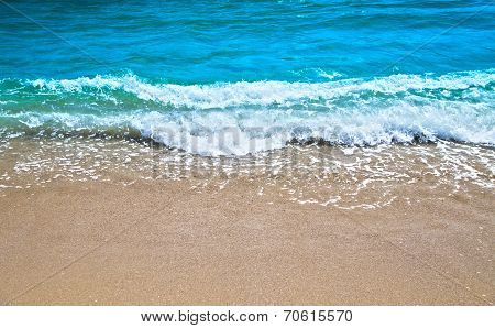 Blue wave gently stroking the sandy shore.