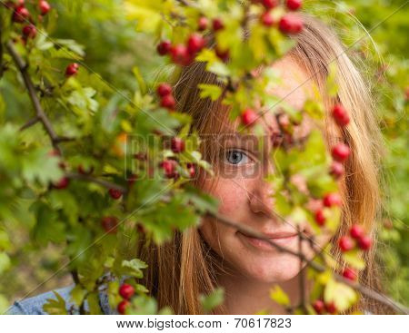 Cute young girl hid in a park amongst flowering shrubs.