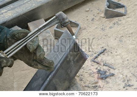 Workers at construction site cutting metal using blowtorch