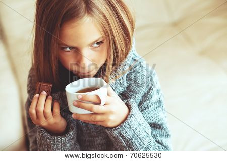 Child wearing sweater and drinking tea at home