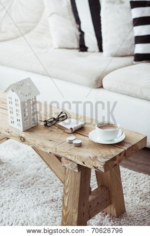 Still life interior details, cup of coffee and a book near white cozy sofa