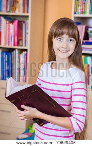 Schoolgirl  holding book in the library