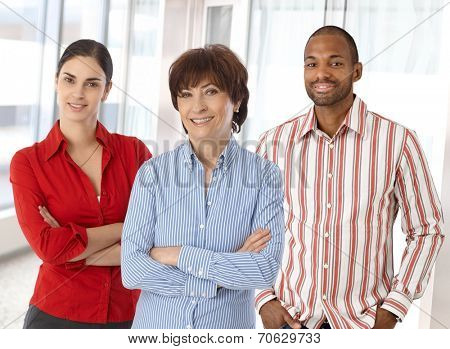 Team of happy caucasian business people standing in office looking at camera smiling, standing, arms crossed.