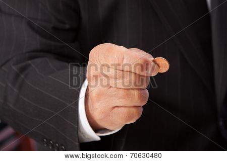 Man's hand pinching penny-horizontal