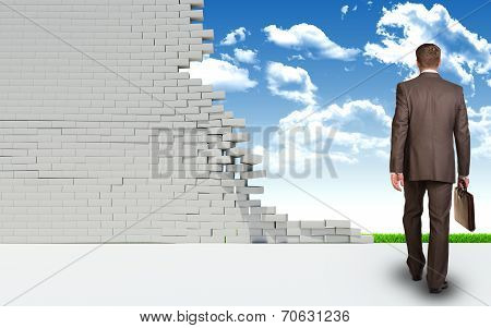 Businessman goes through ruined brick wall