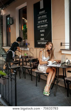 Young business woman in cafe with tablet and laptop