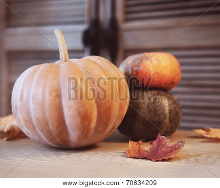 Autumn Pumpkins With Leaves On Wooden Table