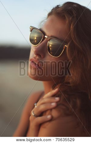 Young beautiful woman with long curly hair in sunglasses