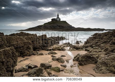 Lighthouse Landscape With Stormy Sky Over Sea With Rocks In Foreground