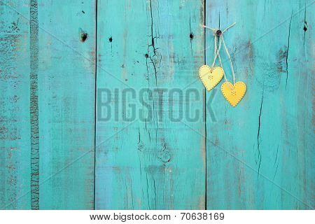 Two gold hearts hanging from rope on antique green weathered wood background
