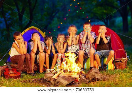 Funny Kids With Painted Faces On Hands Sitting Around Camp Fire