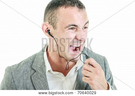 Man Wearing Earbuds Talking On Mobile Phone Shouting