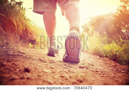 Mans legs hiking down a hill in the countryside
