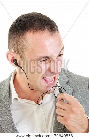 Young Man Using Earbuds Shouting On Microphone