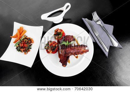fresh red beef meat steak barbecue garnished vegetable salad and basil on white plate over black wooden table with bbq sauce in sauce boat