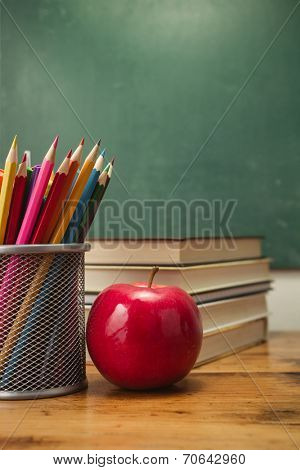 Apple with pencils and stack of books