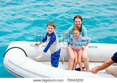 Family with kids having a ride on inflatable dinghy boat