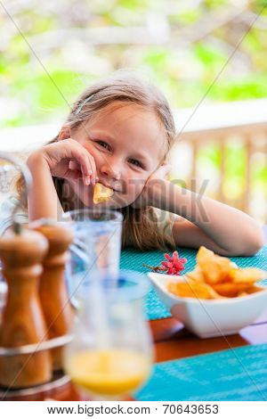 Adorable little girl enjoying eating potato chips at restaurant