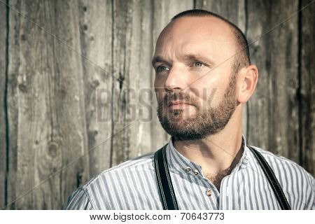 A traditional bavarian man in front of a wooden background