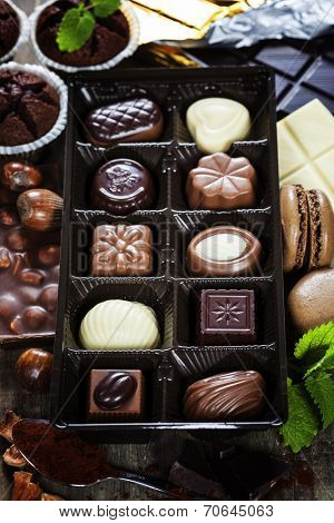 An assortment of fine chocolates in white, dark, and milk chocolate on wooden board