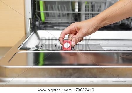 Woman Putting Tablet In Dishwasher Detergent Box