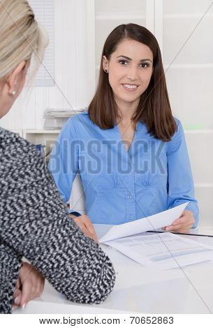Appointment At A Specialist For Finance: Female Customer And Adviser Sitting At Desk Talking About A
