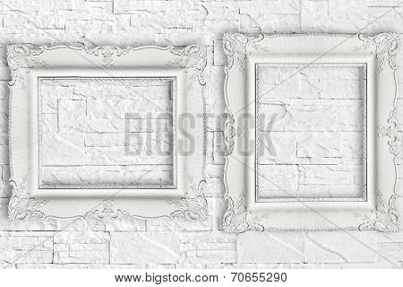 Two white frame on brick wall