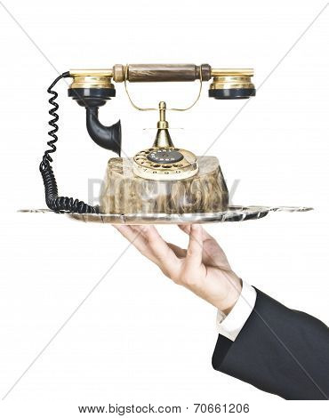Hand holding a silver tray with an old telephone on it