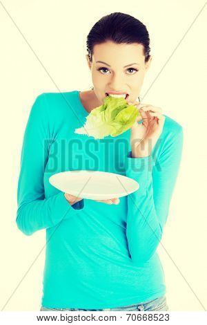 Fit young beautiful woman eating salat, isolated on white