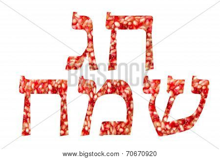 Chag Sameach (Happy holiday) written in hebrew with Pomegranate seeds