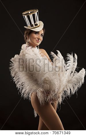 Burlesque dancer in white dress with plumage