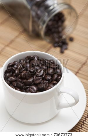 Roasted Coffee Beans In Cup And Bottle.