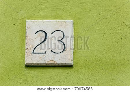 House Number Twenty Three On A Stone Plaque With A Green Wall Background