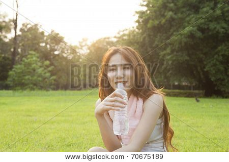 Woman Drinking Water And Sit On Grass.