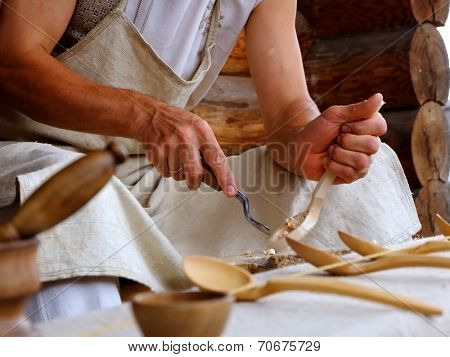 Hands of the craftsman carve a wooden spoon a gouge.