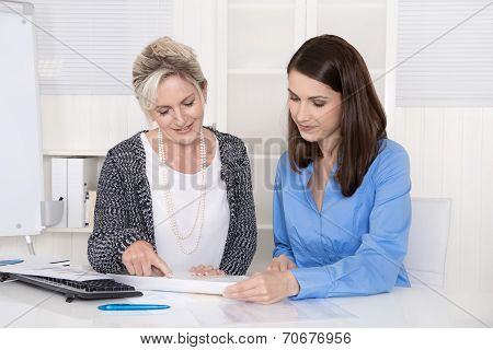 Two Attractive Businesswoman In Meeting Analyzing Budget.